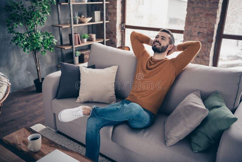 Retrato do seu ele indivíduo satisfeito animador alegre farpado atrativo agradável que senta-se no divã que tem o resto no sótão  fotografia de stock royalty free