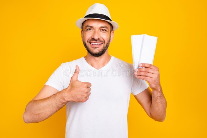 Retrato do seu ele queolha o t-shirt branco vestindo do indivíduo contente animador alegre atrativo que guarda bilhetes disponivé fotografia de stock royalty free