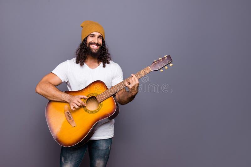 Retrato do seu indivíduo ondulado-de cabelo positivo animador alegre atrativo considerável agradável que joga a guitarra bateu o  imagens de stock