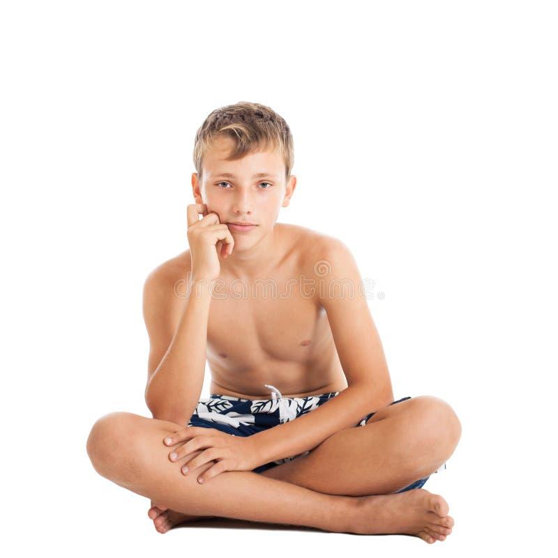 Retrato do short vestindo de uma natação do menino adolescente europeu bonito. Um menino que senta-se no assoalho. fotografia de stock