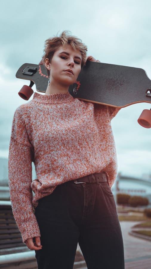 Retrato do skater f?mea novo que guarda seu skate imagem de stock royalty free
