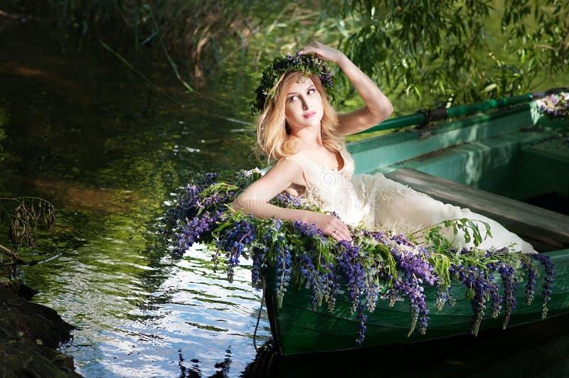 Retrato do slavic ou da mulher Báltico com a grinalda que senta-se no barco com flores verão fotos de stock royalty free