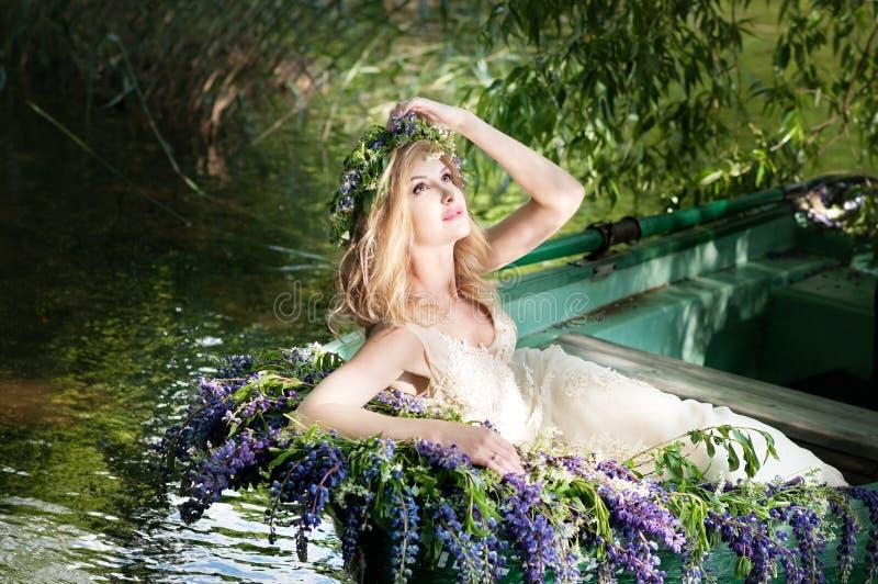Retrato do slavic ou da mulher Báltico com a grinalda que senta-se no barco com flores verão fotografia de stock royalty free