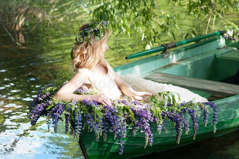 Retrato do slavic ou da mulher Báltico com a grinalda que senta-se no barco com flores verão imagem de stock