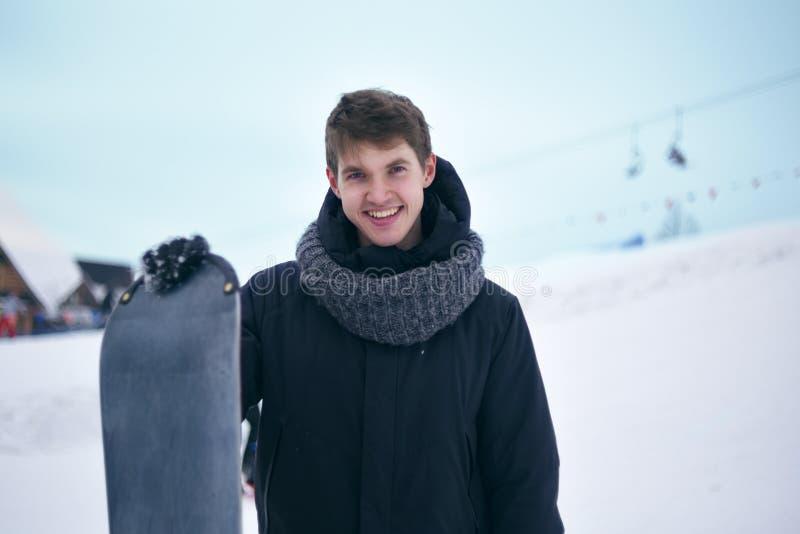 Retrato do snowboarder O homem considerável no terno de esqui está guardando um snowboard, olhando a câmera e o sorriso Homem nas fotografia de stock royalty free