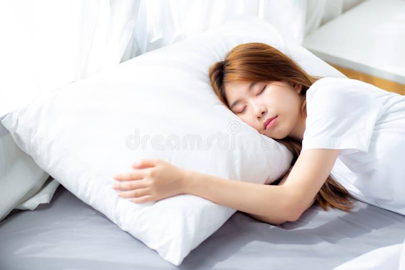 Retrato do sono asiático bonito da jovem mulher que encontra-se na cama com cabeça no descanso confortável e feliz com lazer fotografia de stock royalty free