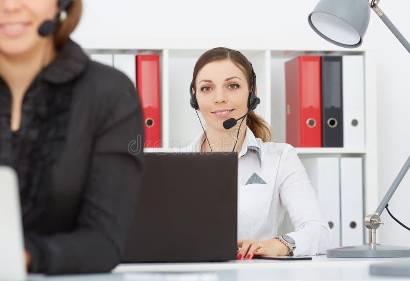 Retrato do sorriso empregado consideravelmente do sexo feminino do serviço de atenção com os auriculares no local de trabalho imagem de stock