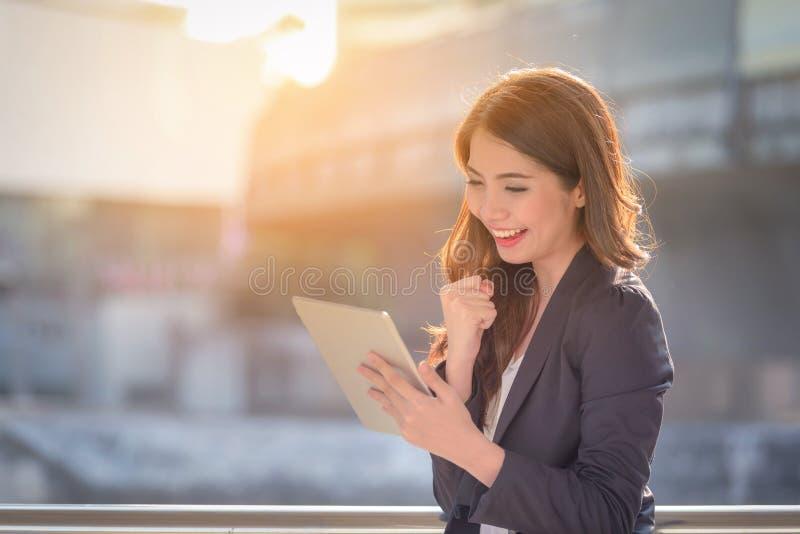 Retrato do sorriso feliz da mulher de negócio que olha a tabuleta digital sobre fotos de stock royalty free