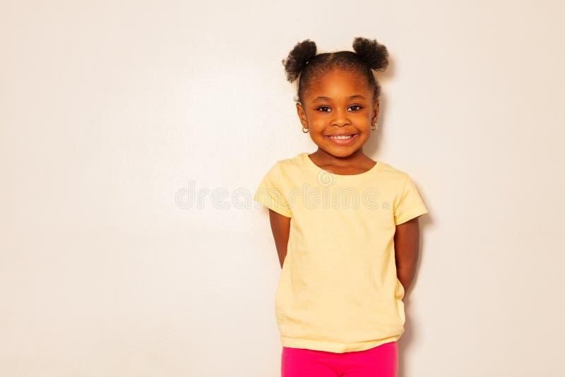 Retrato do sorriso preto pequeno agradável da menina sobre a parede fotos de stock royalty free