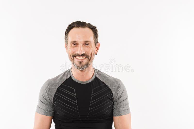 Retrato do sportswear vestindo caucasiano feliz do homem 30s que levanta sobre imagens de stock