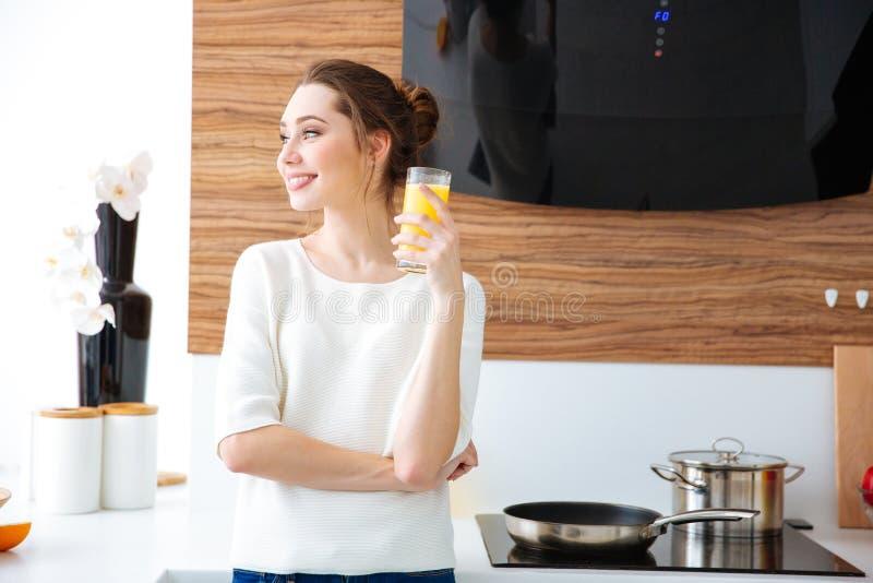 Retrato do suco bebendo da mulher alegre bonita fotografia de stock