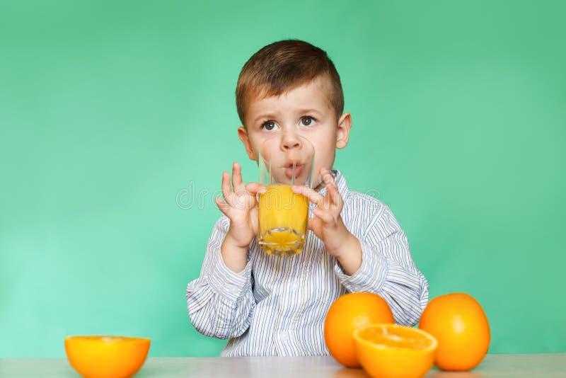Retrato do sumo de laranja bebendo do rapaz pequeno feliz imagem de stock royalty free