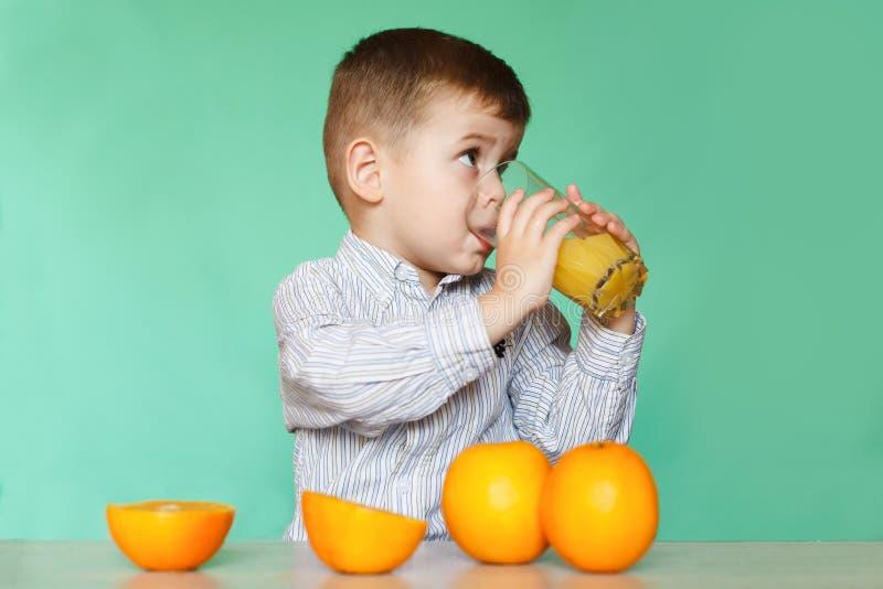 Retrato do sumo de laranja bebendo do rapaz pequeno feliz fotografia de stock royalty free