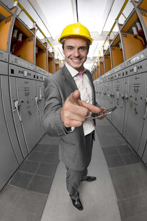 Retrato do supervisor de sorriso novo com PC da tabuleta que aponta em você na sala de comando fotografia de stock royalty free