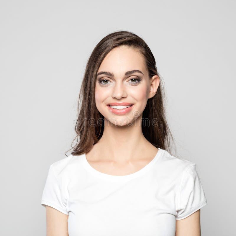 Retrato do t-shirt branco vestindo da jovem mulher bonito imagens de stock