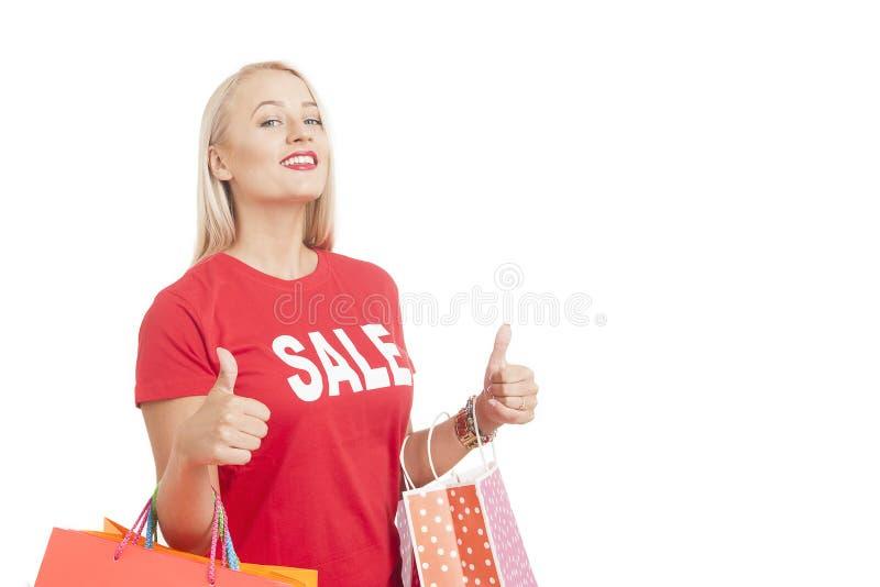 Retrato do t-shirt vestindo da venda da jovem mulher que guarda o saco de compras fotografia de stock royalty free