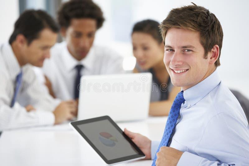 Retrato do tablet pc de utilização executivo masculino com reunião do escritório no fundo