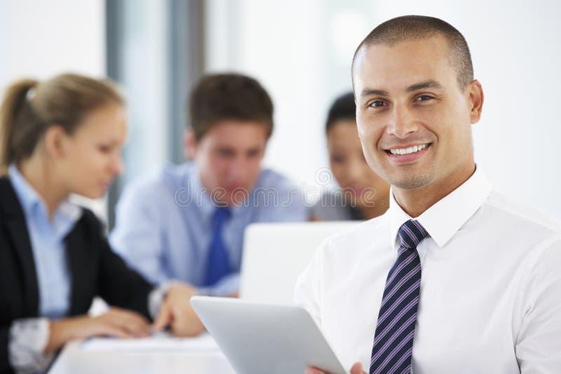Retrato do tablet pc de utilização executivo masculino com reunião do escritório no fundo foto de stock