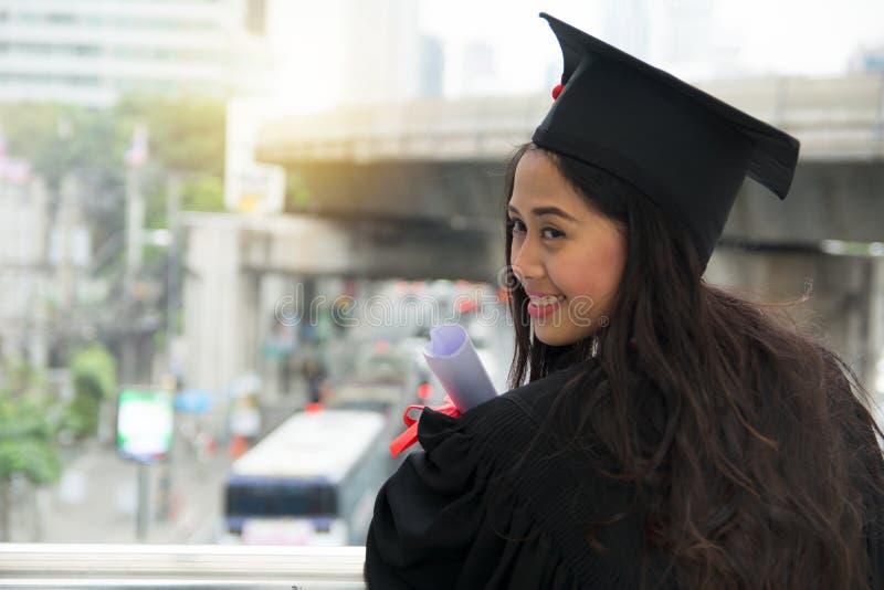 Retrato do tampão vestindo graduado bem sucedido do estudante fêmea e do g foto de stock royalty free