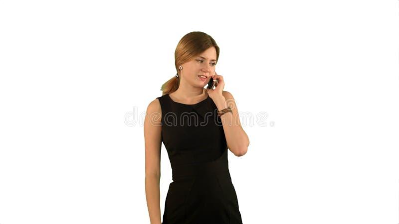 Retrato do telefone de sorriso da mulher de negócio que fala no fundo branco isolado foto de stock