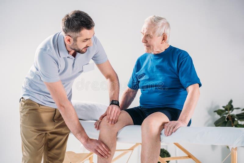 retrato do terapeuta da reabilitação que faz a massagem ao homem superior fotografia de stock