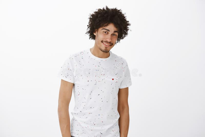 Retrato do tipo encantador e do modelo masculino latino-americano apto com bigode e penteado afro, sorriso flirty e presumido imagem de stock