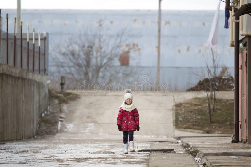 retrato do Tolo-comprimento da menina bonita engraçada nova pequena bonito da criança na roupa morna agradável do inverno que and fotografia de stock