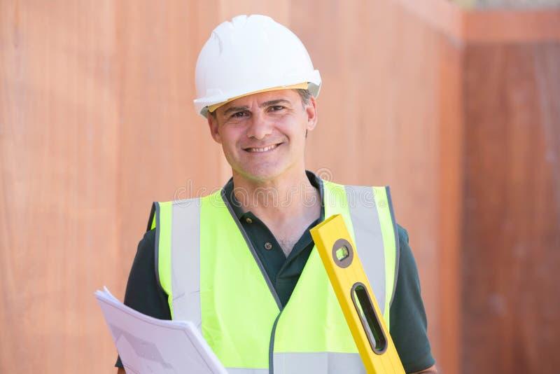 Retrato do trabalhador da construção On Building Site com plano da casa imagens de stock royalty free