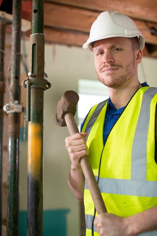 Retrato do trabalhador da construção com malho que demole a parede na casa renovada imagem de stock