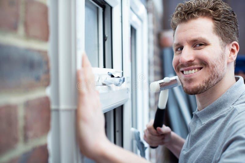 Retrato do trabalhador da construção Installing New Windows na casa foto de stock