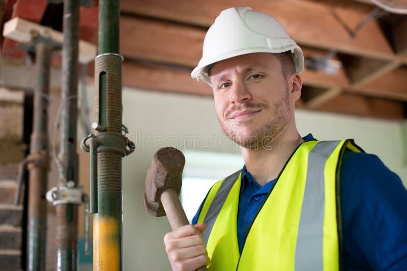 Retrato do trabalhador da constru??o com malho que demole a parede na casa renovada fotografia de stock royalty free
