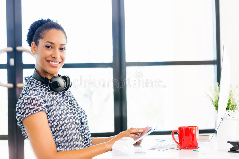 Retrato do trabalhador de escritório afro-americano de sorriso que senta-se no offfice imagens de stock