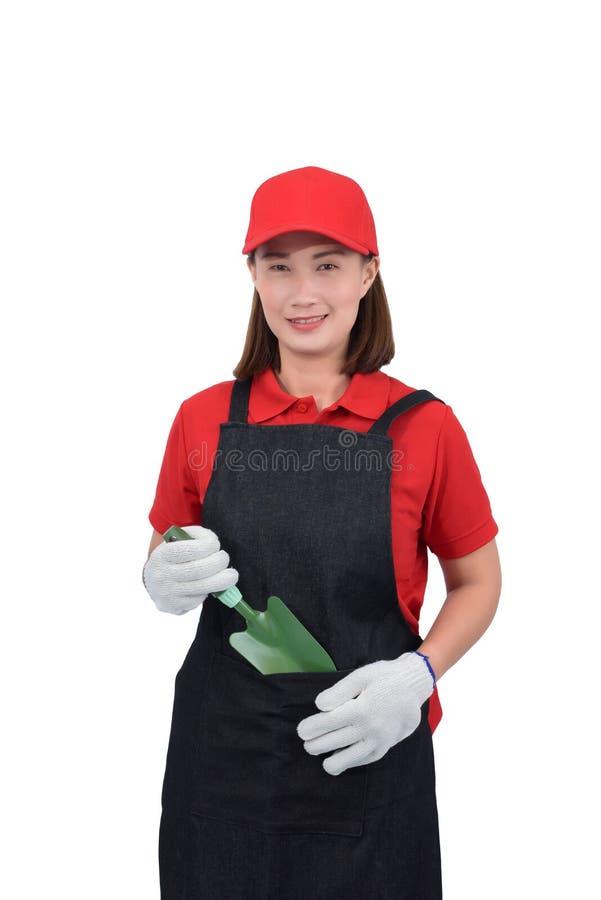 Retrato do trabalhador de jovem mulher que sorri no uniforme vermelho com avental, pá da terra arrendada da mão da luva isolada n imagem de stock royalty free