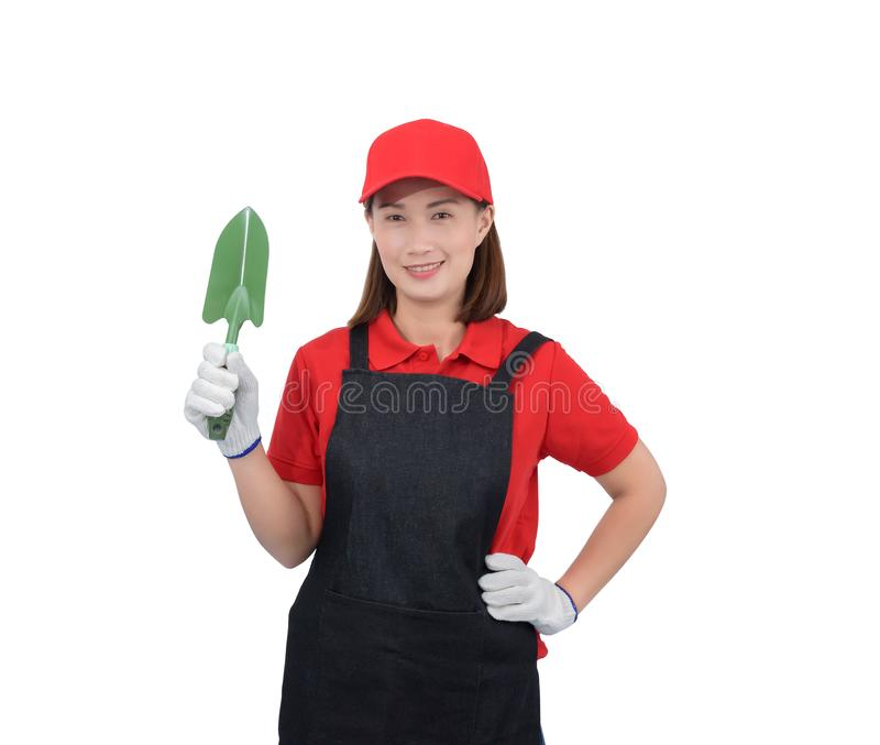 Retrato do trabalhador de jovem mulher que sorri no uniforme vermelho com avental, pá da terra arrendada da mão da luva isolada n fotografia de stock