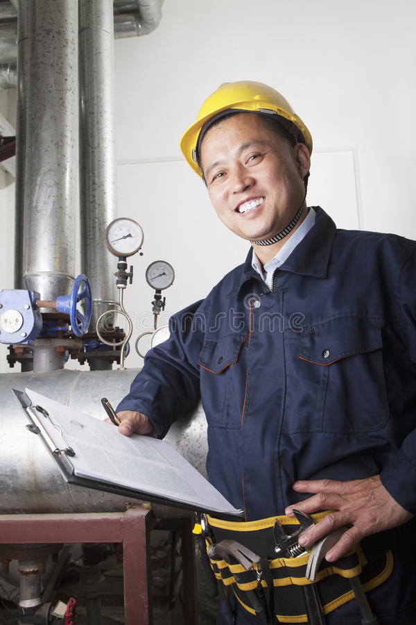 Retrato do trabalhador de sorriso com uma prancheta que verifica o equipamento do oleoduto em uma planta de gás, Pequim, China fotos de stock royalty free