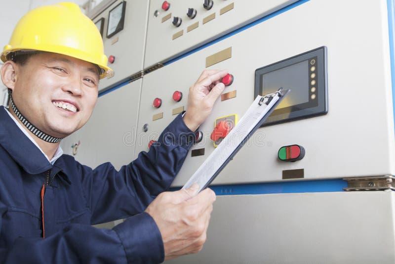 Retrato do trabalhador de sorriso que guarda a prancheta e que verifica controles em uma planta de gás, Pequim, China fotografia de stock