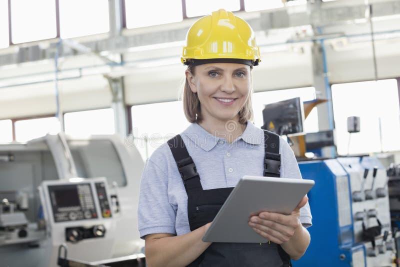 Retrato do trabalhador fêmea de sorriso que usa a tabuleta digital na indústria de transformação fotografia de stock