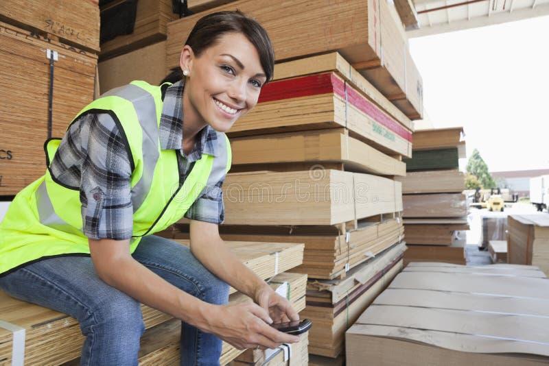 Retrato do trabalhador industrial fêmea que usa o telefone celular ao sentar-se na pilha de pranchas de madeira fotos de stock royalty free