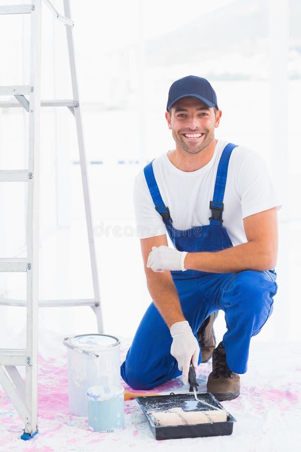 Retrato do trabalhador manual de sorriso que usa o rolo de pintura na bandeja foto de stock