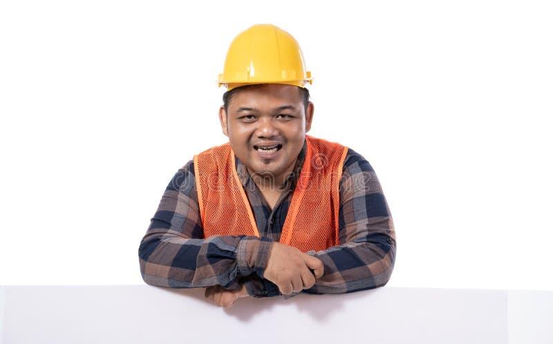 Retrato do trabalhador manual feliz com capacete e do uniforme que inclina-se na placa branca fotografia de stock