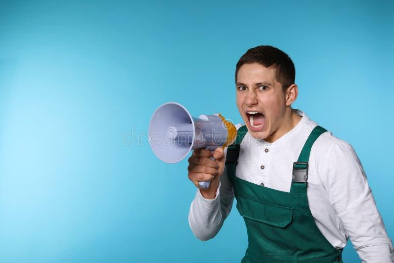 Retrato do trabalhador masculino emocional que usa o megafone no fundo da cor fotografia de stock