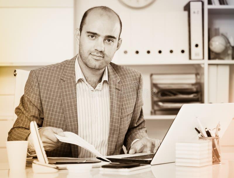 Retrato do trabalhador masculino no assento do escritório imagens de stock
