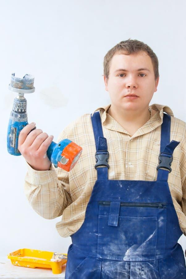 Retrato do trabalhador novo com broca à disposicão fotografia de stock royalty free