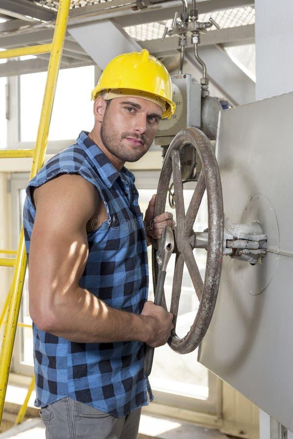 Retrato do trabalhador novo seguro que fixa a válvula industrial imagem de stock