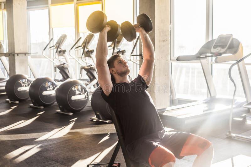 Retrato do treinamento adulto novo do homem do esporte no gym apenas atleta que dá certo em um gym, sentando e guardando o peso d fotos de stock