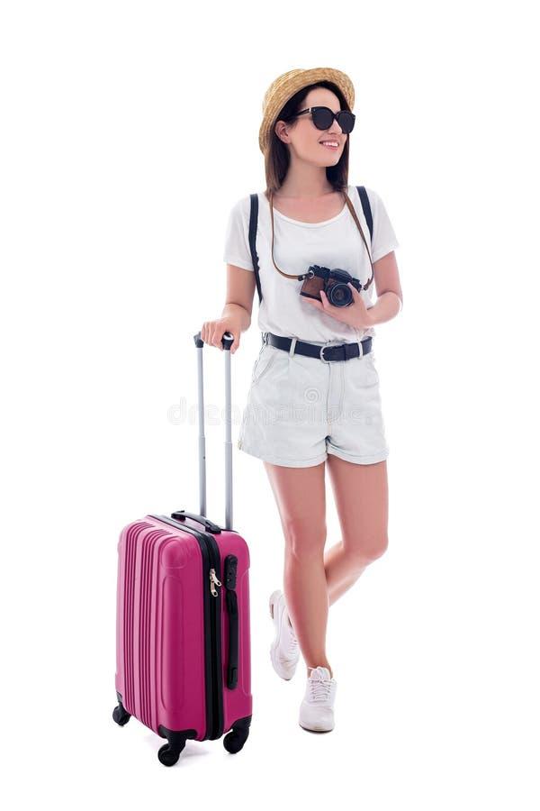 Retrato do turista bonito novo da mulher no chapéu de palha com a mala de viagem, a trouxa e a câmera isoladas no branco fotos de stock