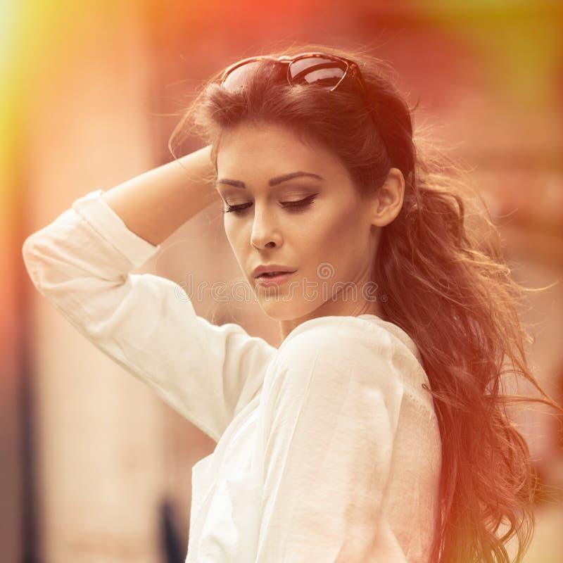 Retrato do verão da jovem mulher fora na camisa e nos óculos de sol brancos vestindo da cidade imagem de stock royalty free