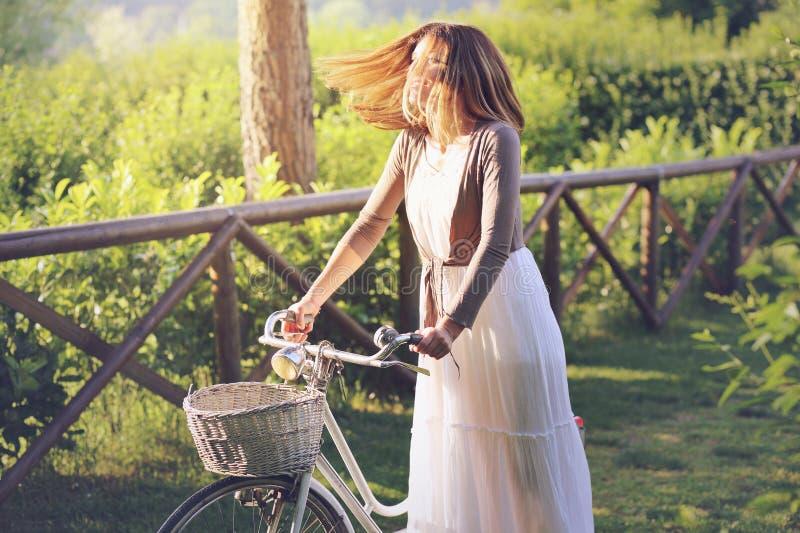 Retrato do verão de uma mulher de sorriso com bicicleta velha imagem de stock royalty free