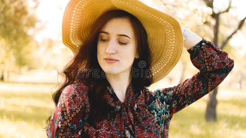 Retrato do ver?o, chap?u de palha vestindo da jovem mulher bonita no tempo do por do sol fotos de stock