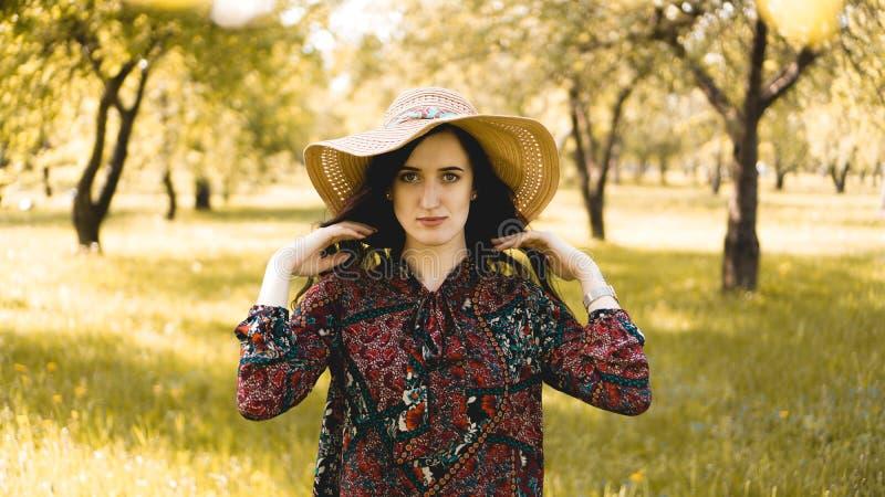 Retrato do ver?o, chap?u de palha vestindo da jovem mulher bonita no tempo do por do sol imagem de stock royalty free